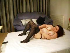 Fat brunette hair wearing black stockings sticks dildo in her corpulent pussy